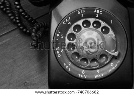 antique telephone on wooden table black and white color for telecommunication concept in close up view