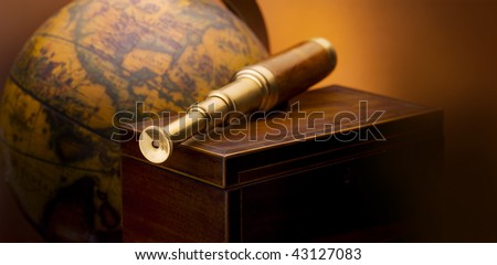 Antique telescope sitting on wooden box with antique map in background- space for copy