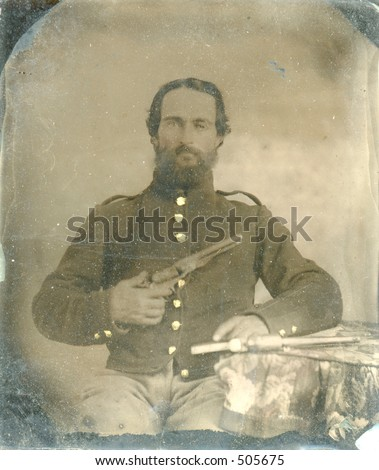 Antique tintype of Civil War soldier holding gun. Around 1860. Lots of intact wear and grunge.