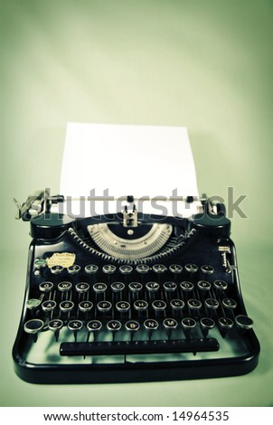 Antique typewriter against a sallow yellow and washed out teal backdrop