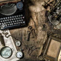 Antique typewriter and vintage office tools on wooden table. Nostalgic still life.