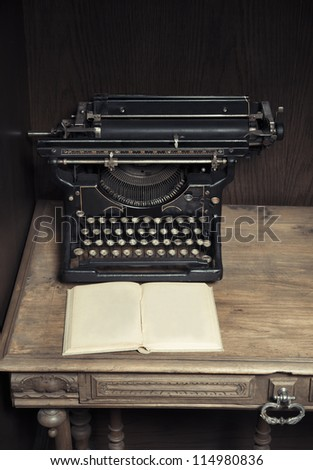 Antique typewriter on desk with book
