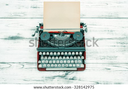 Antique typewriter on wooden table. Vintage style colored picture. German lettering