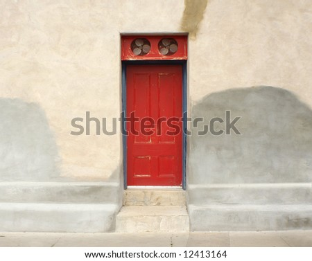 Antique unique red door with fans above it & adobe wall