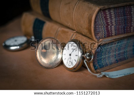Antique vintage silver patina closed case pocket watch with old brown leather bound books. Shallow depth of field and vignetting.