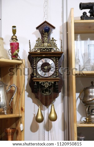 Antique wall clock with pendulum on the flea market #1120950815