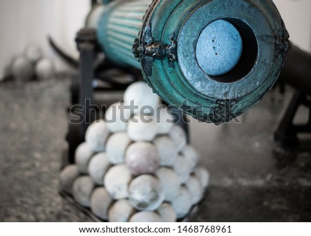 antique war cannon with cannonballs, cannonballs in a stack with vintage cannon, barrel of a gun #1468768961