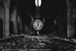 Antique watch with chainlet hanging over heap of bricks and wood in an abandone catholic church. Creepy concept of time. Black and white.