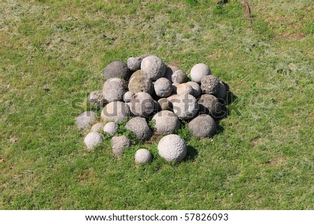 Antique white stone cannonballs on a grass meadow