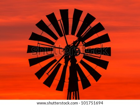 Antique windmill silhouetted by a colorful orange Midwestern sunrise sky