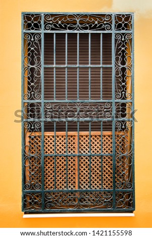 Antique window with wrought metal bars in an ancient building #1421155598