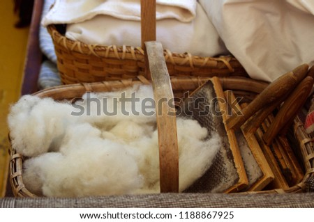 Antique wooden basket with raw wool and comb paddels