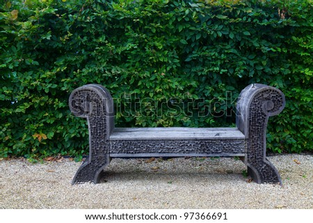 Antique wooden bench on white pebble garden and lush green leaf facade.