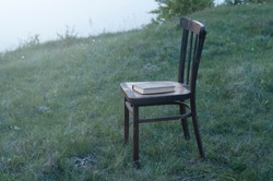 Antique wooden chair and book. Relax on the grass. Loneliness and depression concept.
