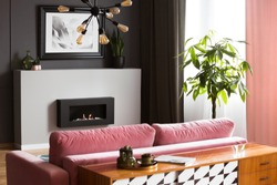 Antique, wooden dresser behind a powder pink, velvet sofa in a bright living room interior with gray walls and a burning fireplace. Real photo.