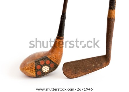 Antique wooden driver and putter -- golf clubs -- against white background.  Shallow depth of field.
