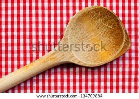Antique wooden spoon for cooking with red white background