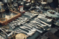 Antiques on flea market or festival, aged vintage silver cultery - spoons, knifes, forks, and other vintage things. Collectibles memorabilia and garage sale concept. Selective focus