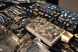 Antiques on flea market or festival - vintage jewelry, silver brooches and other vintage things. Collectibles memorabilia and garage sale concept. Selective focus
