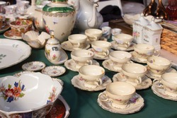 Antiques on flea market or festival - vintage porcelain tea cups, tableware and other vintage things. Collectibles memorabilia and garage sale concept. Selective focus