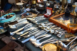 Antiques on flea market or festival, vintage silver cultery - spoons, knifes, forks and other vintage things. Collectibles memorabilia and garage sale concept