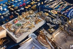 Antiques on flea market or seasonal festival - vintage jewelry, silver brooches and other vintage things. Collectibles memorabilia and garage sale concept. Selective focus