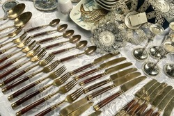 Antiques on flea market, vintage silver cutlery - spoons, knifes, forks and other vintage things. Collectibles memorabilia and garage sale concept. Selective focus