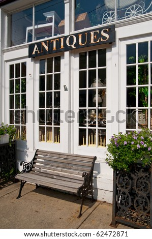 Antiques sign hangs above and a weathered bench sits below the windows of a vintage goods store in a small town.