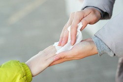 Antiseptic napkin to prevent spread of germs, bacteria, coronavirus, virus. Mother and child on the street disinfecting hands with a wet wipe. Woman cleaning kid hands with antiseptic tissue outdoors.