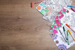 Antistress coloring pages and felt tip pens on wooden table, flat lay. Space for text