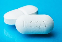 Antiviral drug Hydroxychloroquine (HCQS), two white pills with letters HCQS engraved on the side,potential experimental cure for COVID-19,Coronavirus pandemic outbreak crisis clinical trial medication