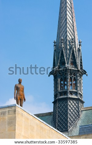 Antony Gormley statue next to the spire of Exeter College chapel, Oxford