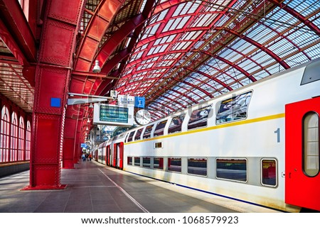 Antwerp, Belgium. Central indoor railway station. Platform made of red metal constructions with clock and panel with departure or arrival schedule. Modern double decker high-speed train.