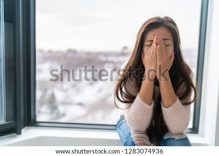 Anxiety winter depression woman having a panic attack and a hard time breathing. Home alone girl crying stressed depressed.