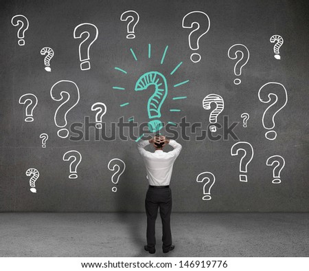 Anxious businessman looking at a drawing of question marks