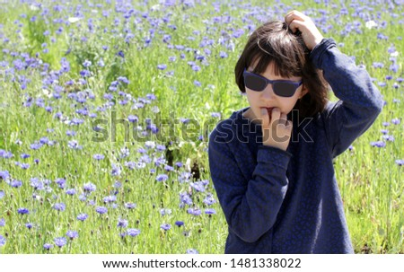 anxious child with sunglasses scratching head questioning, having concerns or worries, seeking for idea or solution over a cornflower field, outdoor