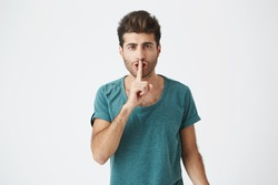 Anxious serious man wearing casual t-shirt holding index finger at his lips, asking to keep silent and not to make noize. Human facial expressions.
