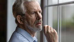 Anxious worried elderly man feel nervous pessimistic look at window wait for someone has mental health problems think of death. Sick abandoned grandpa suffer of loneliness at home in retirement center