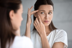 Anxious young woman look in the mirror worried about wrinkle or acne on unhealthy skin, upset unhappy millennial female examine squeeze pimple on face, cosmetology, skincare concept