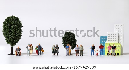 Any of various miniature families standing in front of miniature trees and miniature building.