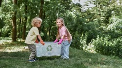Anything that can be recycled. Two cute little boy and girl holding recycle bin with plastic waste while standing in the forest or park. Environmental conservation and ecology concept