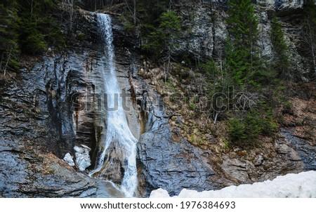 Apa Spanzurata waterfall flowing of a sharp stone wall during early springtime. Snow is melting increasing the cascade's volume. Latorita Mountains, Carpathia, Romania. Stok fotoğraf ©