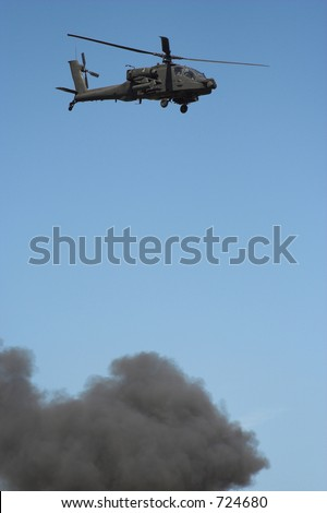 Apache helicopter in flight in a war zone