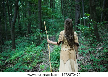 Apache tribe scout looking for tracks in the woods, beautiful native american female warrior looking for footprints in the forest, indian dress concept