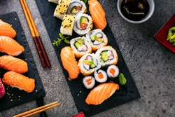 apanese sushi food. Maki ands rolls with tuna, salmon, shrimp, crab and avocado. Top view of assorted sushi. Rainbow sushi roll, uramaki, hosomaki and nigiri