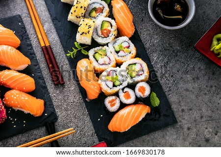 apanese sushi food. Maki ands rolls with tuna, salmon, shrimp, crab and avocado. Top view of assorted sushi. Rainbow sushi roll, uramaki, hosomaki and nigiri