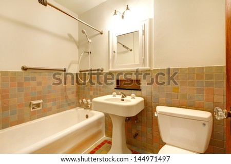 Apartment Bathroom with old antique fixtures and white tub.