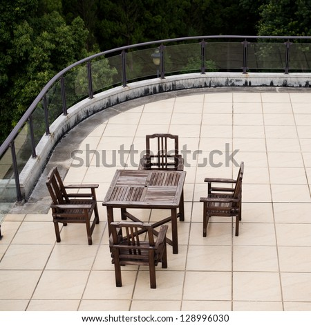 Apartment building roof top terrace exterior with table and chairs.