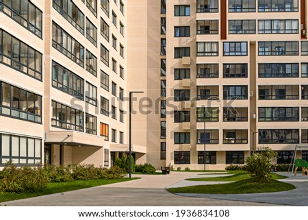 apartment building with colorful facades. Modern minimalistic architecture with lots of square glass Windows and flowers on the building.