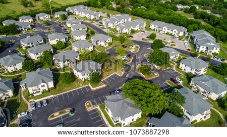 Apartment buildings and multistory townhomes a new development urban housing and Austin living - Aerial drone view - modern curved roads and large square two story townhomes